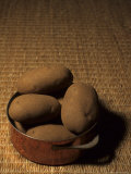 A Group of Baking Potatoes Sit in a Brass Cooking Pot