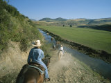 A Group of Cowboys and Cowgirls Cross a Stream on a Ranch