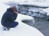 Man Photographing River in Winter
