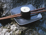 Elegant Sushi and Chopsticks Beside Rushing Water