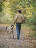Man Walking a Dog Through Autumn Park