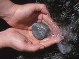 Person Holding Rock with the Word Friend in Rushing Water