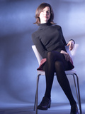 Seated Woman in Black Turtleneck and Skirt