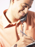 Man Talking on Telephone and Writing in Day Planner