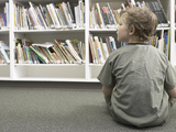 Little Boy Looking Rows of Books on Library Shelves