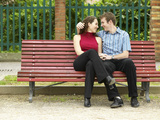 Smiling Couple Sitting on Park Bench