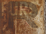 Close-up of Faded Lettering on a Rusty Metal Surface