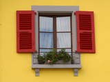 A Yellow House and a Window with Red Shutters and a Flower Box