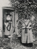 Two Welshwomen in Traditional Dress Stand Outside Their Cottage with a Spinning Wheel