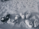 Four Pairs of Shoes on the Sand
