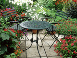 Metal Table and Chairs on Patio Backed by Pots with Lilium Longifolium