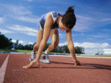 Close-up of a Female Athlete in The Starting Position on a Running Track