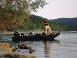 Man Standing in a Boat Fishing