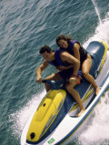 Mid Adult Couple Riding a Jet Ski in the Sea