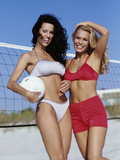 Portrait of Two Young Women Standing on the Beach with a Volleyball