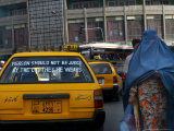 An Afghan Woman Clad in a Burqa Walks Next to a Taxi in Kabul  Afghanistan  Wednesday  June 7  2006
