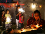 A Woman Lights Earthen Lamps as Children Ignite Firecrackers in New Delhi
