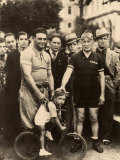 Two Cyclist Pose with a Little Boy Riding a Small Bike Behind Them  a Group of Men