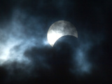 Seen Through Clouds the Sun is Partially Obscured by the Moon During an Eclipse