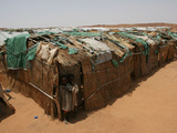 Two Sudanese Boys Stand by Makeshift Huts