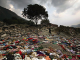A Pakistani Refugee Walks Past Clothing Left Strewn on the Ground