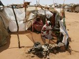 Two Sudanese Women Sit at a Make Shift Hut