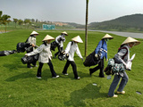 Women Wearing the Traditional Vietnamese Conical Hats Haul Golf Clubs