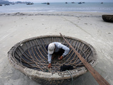 A Vietnamese Fisherman Does Repairs on His Basket Boat on a Beach