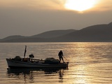 Lone Fisherman Casts His Net at Twilight off the Adriatic Coast
