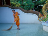 Young Buddhist Monk Sweeps Grounds at Wat Chaimong Khon Along Ping River at Sunset  Thailand