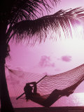 Woman Relaxing in a Hammock on the Beach at Sunset