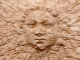Close-up of a Carved Sun Face on a Cracked Stone Wall