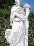 White Stone Sculpture of Woman Carrying Cornucopia