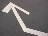 A White Arrow on Gray Pavement