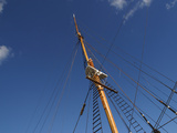 A Tall Ship Mast with Rigging and Ropes Against a Blue Sky
