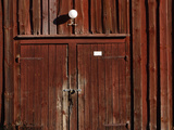 A Dark Wooden Barn Wall and Door with Weathered Boards and Faded Red Paint