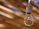 Close-up of a Single Bare Light Bulb Against a Blurred Background