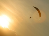 Bright Orange Sunlight with a Parachuter in the Sky