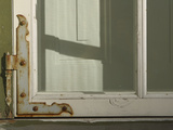 Close-up of a White Window Frame with a Rusty Metal Hinge