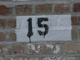 A Brick Wall with a White Painted Square with a Black Number