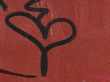 Close-up of a Red Wall and a Black Grafiti Heart Shape