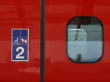 A Window in the Door of a Red Train Car with a Sign and Number