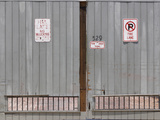 Gray Warehouse Doors with White Signs and Faded Red Lettering