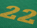 Green Surface with Rough Texture with Bright Yellow Painted Numbers