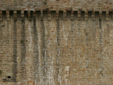 A Weathered Brick Wall with Streaks of Dirt and Water Stains