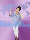 A Woman Drawing a Line Above a Bar Graph While Looknig at a World Map