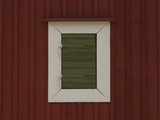 A Single Window on a Red Barn with a White Frame and a Green Shutter