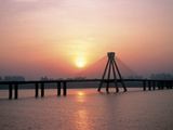 Bright Sunset with Suspension Bridge Over Water