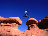 A Man Jumps onto a Hoo-Doo Formation in Goblin Valley  Goblin Valley State Park  Utah  USA