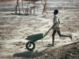 Boy Running with Wheelbarrow  Burkina Faso